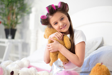 Lovely girl hugging her toy bear sitting on bed. Little preschooler with hair curlers in her hair holding stuffed animal in her bedroom.