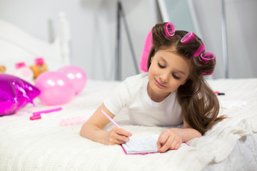 Sweet young lady writing down while laying on her white bed. Little preschooler scribbling some notes into her notebook while laying on bed.