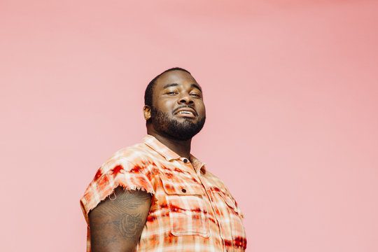 Portrait of a cool  plus size man in orange shirt on pink background