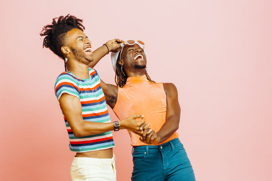 Having fun in a relationship  - portrait of two men holding hands and laughing hard