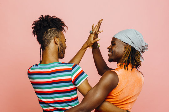 Having fun in a relationship - portrait of two men holding hands and dancing
