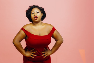Confident curvy woman in red dress with hands on waist