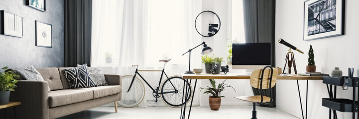 An urban bicycle in a hipster living room interior with a big desk and computer in the workspace area and wooden furniture with industrial elements Fototapete