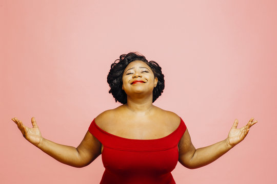 Life is wonderful/ Portrait of a confident, satisfied and happy woman with both hands out, isolated on pink