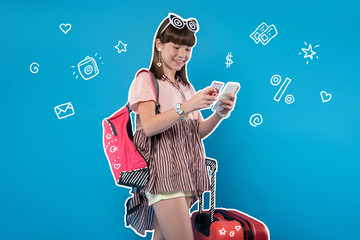 Mobile money. Cheerful teenage girl standing near her big suitcase and putting money on her mobile account before starting a long journey