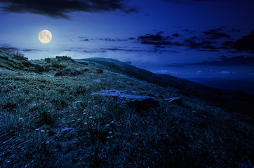 rocks on grassy hillside of the mountain at night