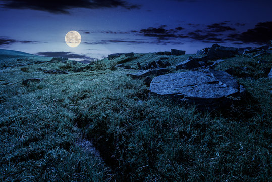 cloud over the grassy hillside with rocks at night