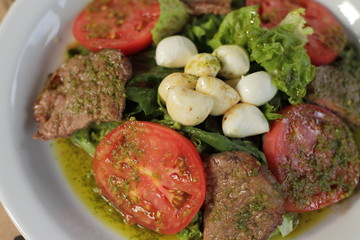 beef and tomatoes salad with mozzarella cheese and pesto sauce