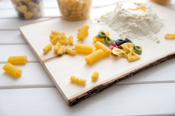 Paste theme. Different kinds of pasta on a wooden background. Fa