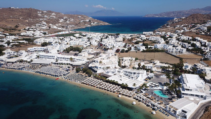 Aerial drone bird's eye view photo of famous organized with sun beds crystal clear water beach of Ornos in island of Mykonos, Cyclades, Greece