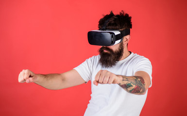 Virtual driving lessons concept. Hipster on confident face driving bike in virtual reality with modern digital gadget. Man with beard in VR glasses driving motorbike, red background