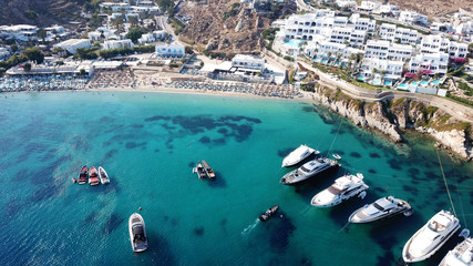 Aerial drone photo of famous pool resorts on top of rocky emerald seascape in iconic island of Mykonos, Psarou beach near Platy Gialos, Cyclades, Greece