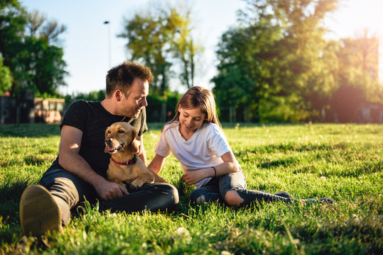 Father and daughter relaxing at park with dog