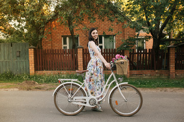 Smiling brunnete happy girl in a white-flowers dress with pink peones and vintage bicycle. Lovely house is on the background