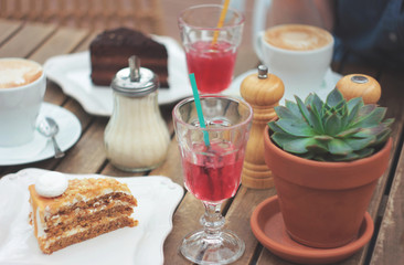 Wooden table on the summer terrace with cake, berry juice, succulent in a clay pot