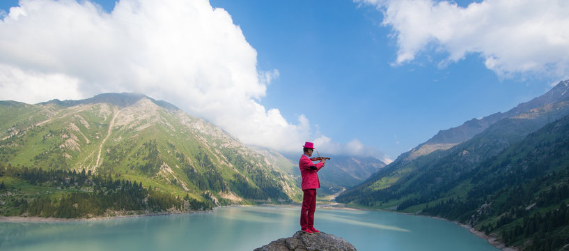 violinist in a red suit playing the violin on the background of a mountain lake