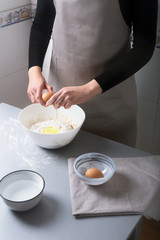 Woman on the home kitchen prepares the dough with flour to make organic pan, bread or pasta