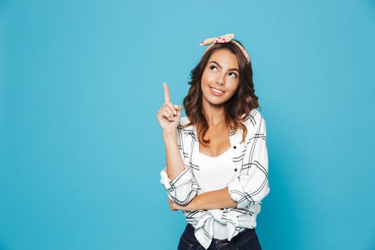 Portrait of lovely excited woman 20s wearing headband smiling and pointing finger upward at copyspace, isolated over blue background