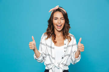 Portrait of lovely brunette woman 20s wearing headband smiling and showing thumbs up, isolated over blue background