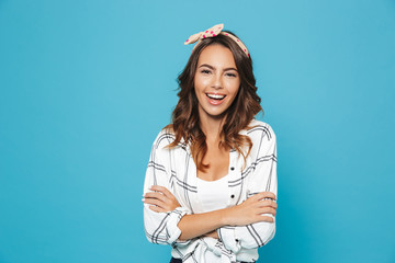 Photo of european brunette woman 20s wearing headband smiling and standing with arms crossed, isolated over blue background
