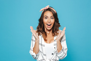 Portrait of lovely brunette woman 20s wearing casual smiling and raising up hands at face, isolated over blue background