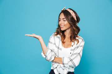 Image of european pretty girl 20s wearing casual clothing smiling and holding copyspace on hand, isolated over blue background