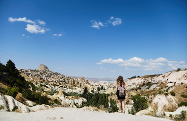 Young girl looking at the landscape. She admires the nature of Cappadocia.