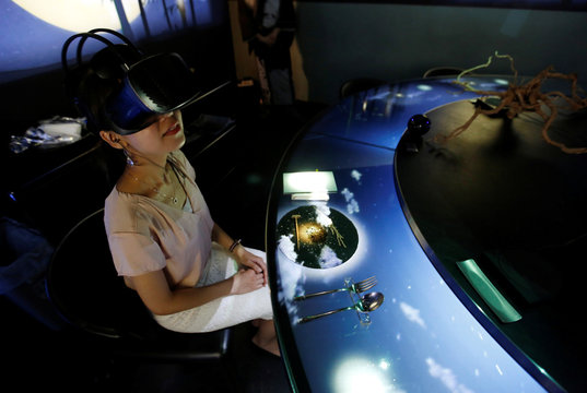 """A woman wears VR glasses while the projection mapping is cast on table and walls during its media preview at """"TREE BY NAKED, yoyogi park"""" restaurant in Tokyo"""
