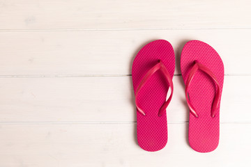pink flip flops on white wooden background with copy space