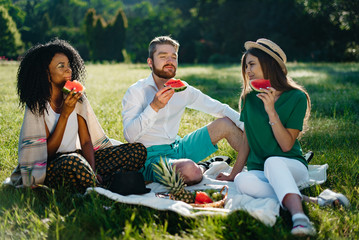 Picnic of three multi race friends. Beautiful african woman and her caucasian male and female friends are enjoying the watermelon.