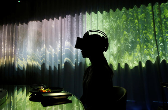 """A woman wears VR glasses while the projection mapping is cast on a table and walls during its media preview at """"TREE BY NAKED, yoyogi park"""" restaurant in Tokyo"""