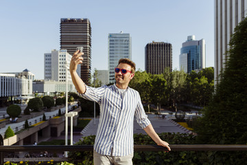 Man leaning on fence and taking selfie with smartphone