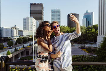 Young couple taking selfie on street