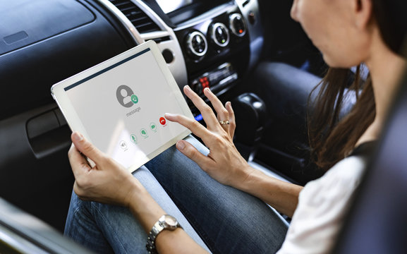 Woman using a digital tablet in the car