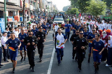 Former Indonesian Badminton player Sigit Budiarto carries the Asian Games torch at the beginning of Asian Games 2018 torch relay ahead of the August 18 - September 2 games held in Jakarta and Palembang, in Yogyakarta