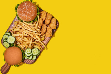 Wooden board with different fast food: burgers, chicken nuggets, french fries on yellow background