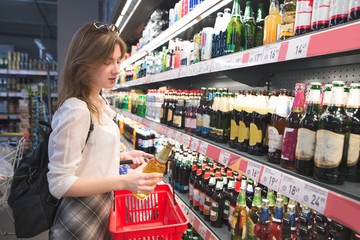 Portrait of an attractive girl who chooses beer in a supermarket. A woman with a red basket buys a beer in a supermarket. Shopping in a supermarket concept