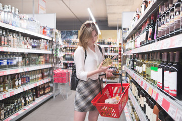Young woman is in the alcohol department of a supermarket with a bottle of wine in her hands and looks at the label. Stylish girl chooses wine at a supermarket.