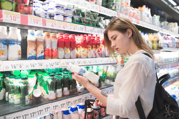 Portrait of a pretty girl standing in the milk department of the supermarket and looking at the yogurt in her hands. Attractive woman chooses yogurt in a supermarket.