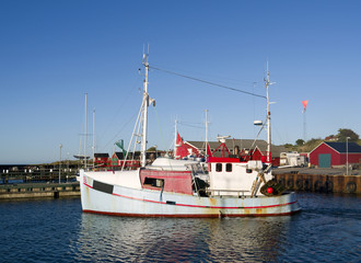 Laesoe / Denmark: A small fishing cutter leaves the harbor of Vesteroe Havn