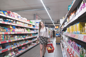 Stylish young woman walking in a supermarket with a basket in her hands and choosing products. Atractive girl buys goods in a big store. Buyer walks through the supermarket and makes purchases