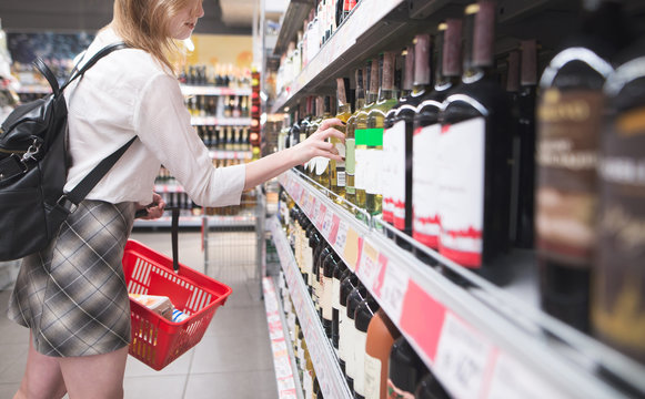 Stylish woman with a red shopping basket in her hands takes a bottle of wine from the supermarket shelf. Girl buys wine in the alcohol department of the supermarket.