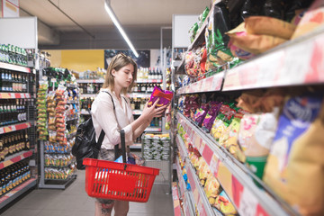 Girl with a red basket in her hands chooses chips from the shelves of the supermarket. Attractive young woman buys chips in the snack department at the supermarket. Shopping in a supermarket concept