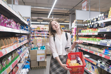Smiling young woman stands in a supermarket with a shopping cart in her hands and looks at the camera. Portrait of a happy stylish woman doing shopping in a supermarket.