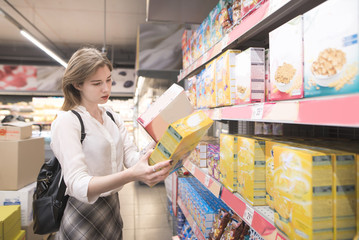 Portrait of a pretty girl who buys flakes in a supermarket. Woman chooses a box of quick breakfasts at the store.
