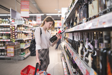 Woman with a red shopping bag chooses alcohol in a supermarket. Selection of products in the supermarket. Choice of wine in the store.
