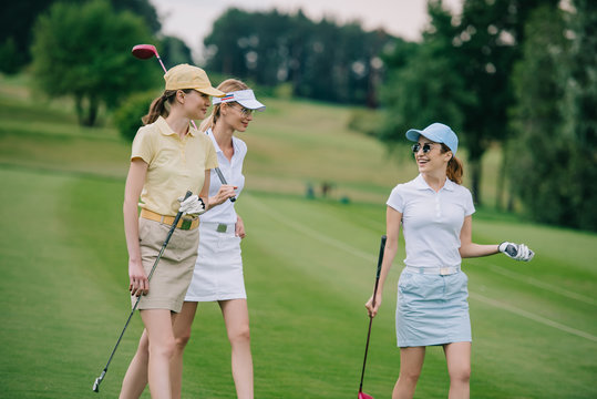 women in caps with golf equipment having conversation at golf course