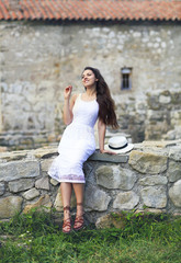 Stylish brunette woman in white dress on background of brick wall