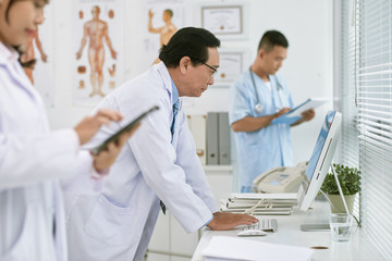 Doctor reading data on computer screen