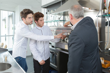 young waiters learning to use coffee machine